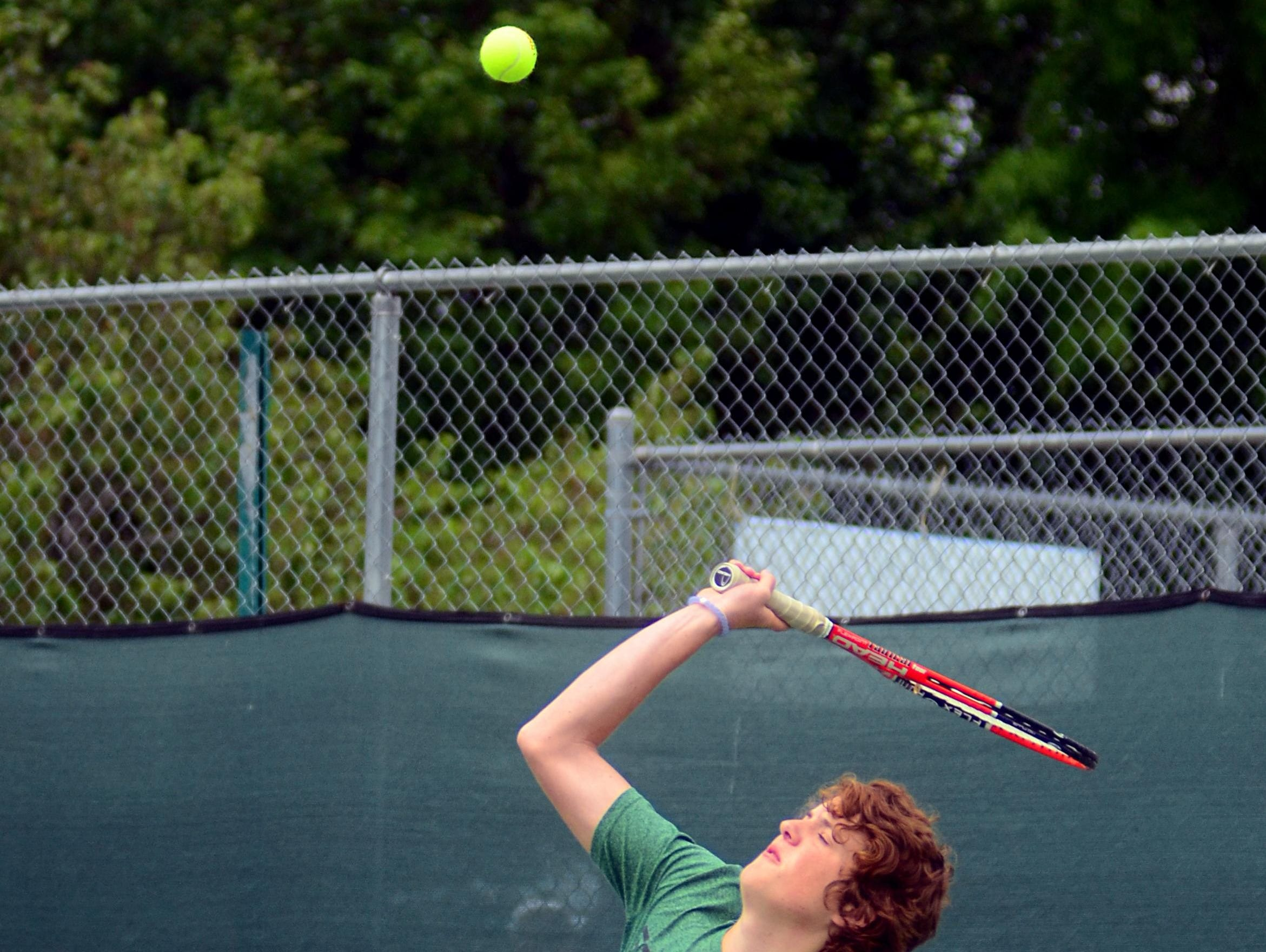 Gallatin High junior Justin White hits a serve during his first-round singles match on Tuesday at the District 9-AAA Individual Tennis Tournament.