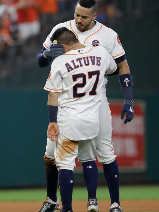Houston Astros' Jose Altuve hugs Carlos Correa after scoring the game-winning run during the ninth inning of Game 2 of baseball's American League Championship Series against the New York Yankees Saturday, Oct. 14, 2017, in Houston. The Astros won 2-1 to take a 2-0 lead in the series. (AP Photo/David J. Phillip)
