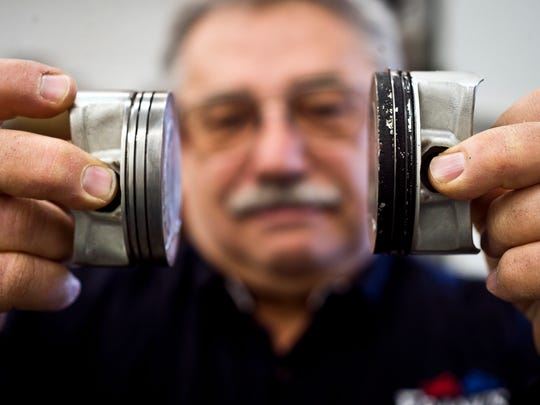 Lester Pelkey, owner of Frank's Motorcycles Sales & Services in Essex Junction, holds up two piston heads. The piston head on the right shows the effects of using gasoline blended with corn ethanol, Pelkey said.