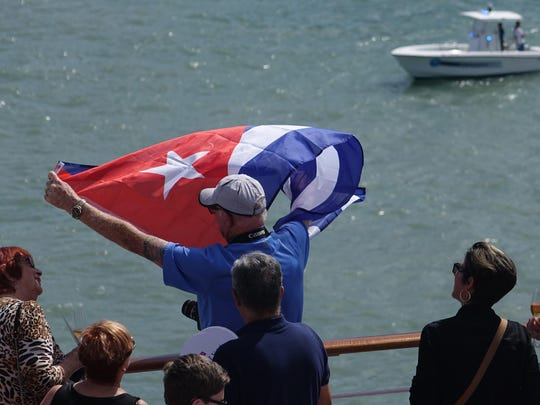 Rick Schneider of Delray Beach waves a Cuban flag onboard the Adonia as the ship leaves port in Miami, Sunday, May 1, 2016, en route to Cuba. After a half-century of waiting, passengers finally set sail on Sunday from Miami on an historic cruise to Cuba. Carnival's Cuba cruises, operating under its Fathom band, will visit the ports of Havana, Cienfuegos and Santiago de Cuba. (Joe Cavaretta/South Florida Sun-Sentinel via AP) MAGS OUT; MANDATORY CREDIT