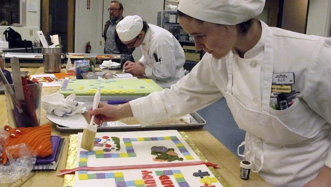 Students Allie Trojano, front, and Deron Noel, rear, work on dessert projects during a class at the New England Culinary Institute in Montpelier.