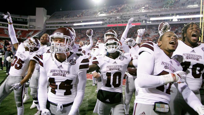 Mississippi State players celebrate with fans after an NCAA college football game against Arkansas, Saturday, Nov. 21, 2015, in Fayetteville, Ark.