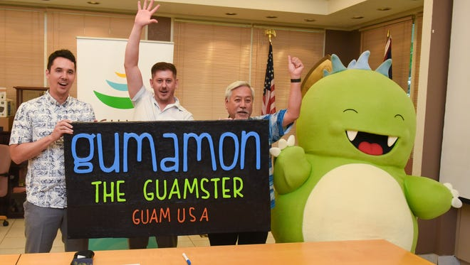 "Asher Goldenberg, center, Guamster, LLC CEO, raises his arm into the air in celebration after the announcement was made of the renaming of the ""Guamzilla,"" a trash eating mascot, to ""Gumamon"" during a press conference at the Guam Visitors Bureau office in Tumon on Friday. From left: Nate Denight, Guam Visitors Bureau president and CEO; Goldenberg; Milton Norinaga, GVB board chairman and Gumamon."
