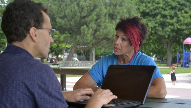 "Brother Steve Herro types responses on his laptop as he interviews Jayme Laabs at Fisk Park in Green Bay this summer for the Bay Area Community Council's ""Connecting Our Community From Many Directions"" project."
