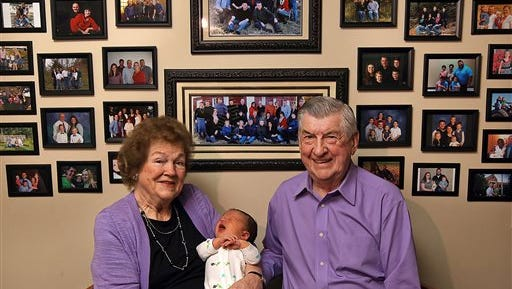 "In this April 17, 2015 photo, Leo and Ruth Zanger sit with their 100th grandchild, Jaxton Zanger, in Leo's real estate office in Quincy, Ill. Jaxton was born April 8 to parents Austin and Ashleigh Zanger. For the numerically inclined, Jaxton was also No. 46 among the great-grandchildren. The Zangers also have 53 grandkids and one great-great-grandchild for a nice round 100. ""The good Lord has just kept sending them,"" Leo Zanger said of the grandkids. ""We could start our own town."""