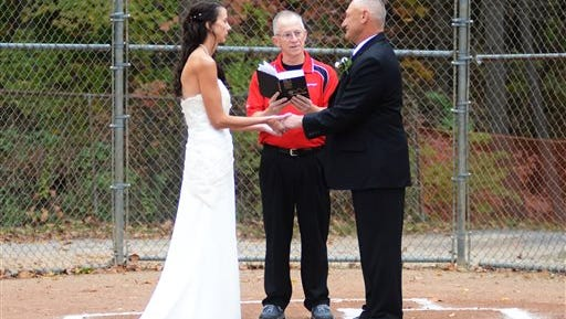 Jerry Shiflett, center, marries Debbie Gould and Larry Castee at Pam Berry Field in White Park, in Morgantown, W.V., Saturday, Oct. 17, 2015. The couple, who first met nine years ago on a softball diamond, decided to team up there, too, tying the knot at home plate. The ballpark theme was complete with the wedding party attired in softball uniforms. (Michaela Michael/The Dominion-Post via AP)