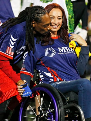 Snoop Dogg kisses the cheek of Olympic champion Amy Van Dyken at Game of Honor, a charity game between NFL Alumni and  Wounded Warriors Amputee Football game played at Shadow Mountain High School on Wednesday, Jan. 28, 2015, in Phoenix. Van Dyken, a six-time Olympic gold medalist, was riding an ATV when she crashed June 6 in Show Low. She survived a six-hour spinal fusion surgery but was left paralyzed from the waist down.