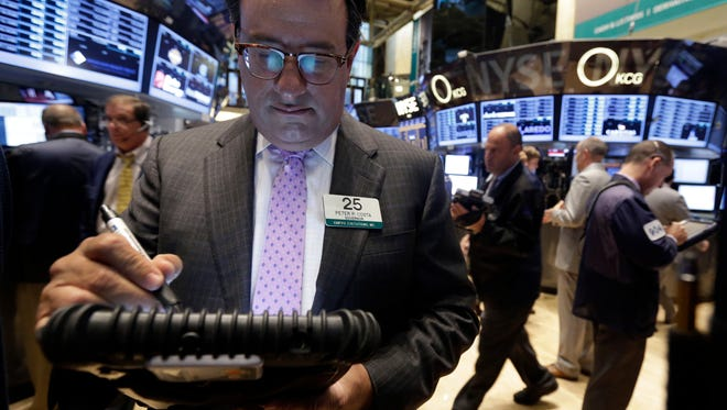 Trader Peter Costa, left, works on the floor of the New York Stock Exchange Wednesday, Sept. 18, 2013.  Stocks were little changed in early trading Wednesday as investors wait to hear from the Federal Reserve on the fate of the central bank's bond-buying program. (AP Photo/Richard Drew) ORG XMIT: NYRD107
