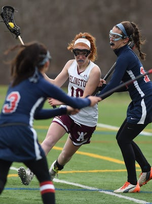 Arlington senior midfielder Abby Carlin tries to shake two Wappingers defenders in a game last April.