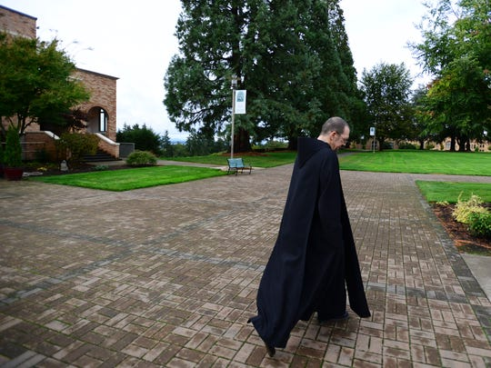 Brother Andre Love, a Benedictine monk, walks to the church to pray at the Mount Angel Abbey. Love is curator of the Abbey's art collection.