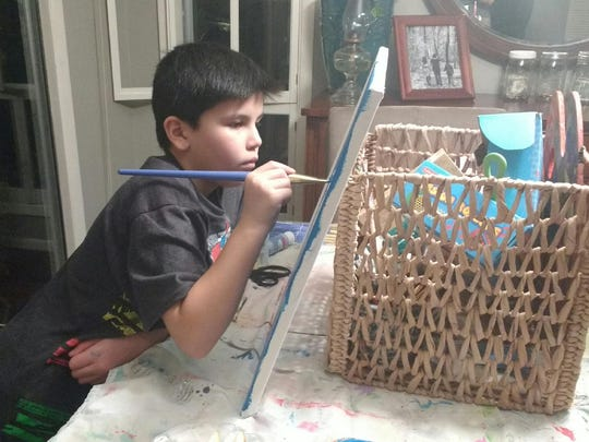 Solen Lewis, 9, works on a painting at his Salem home.