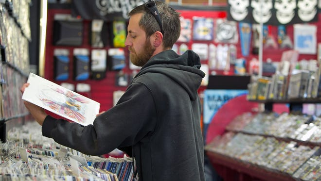 Tony Cochran, of Phoenix, looks at records at a Zia Record Exchange.