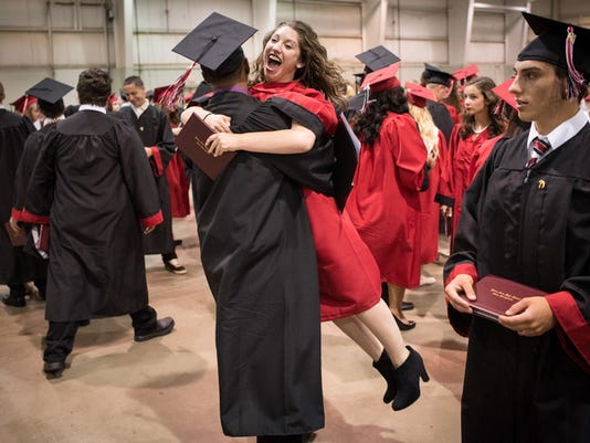 Katie Harper jumps into the arms of Quaadir Otto after both graduated from Dover Area High School in 2014.