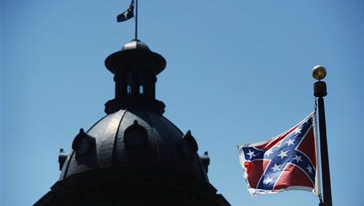 In a Friday, June 19  file photo, the Confederate flag flies near the South Carolina Statehouse, in Columbia, S.C.