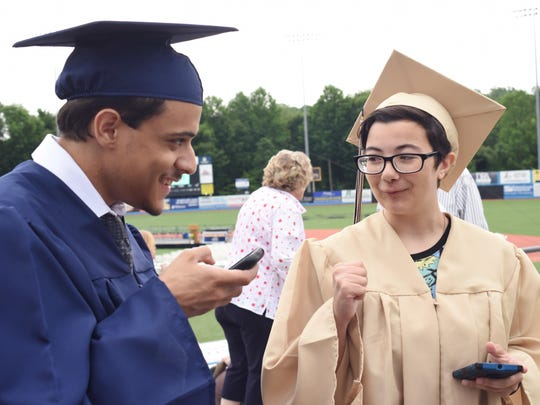 From left, Brooklyn Kyle and Alex Nivel check their phones prior to the start of Beacon High School's commencement ceremony on Saturday. Kyle is attending Dutchess Community College, and Nivel is attending DCC North in the fall.