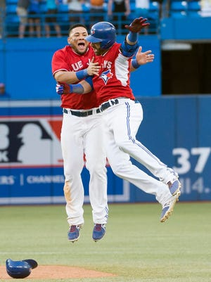 Jose Bautista, right, celebrates his game-winning RBI with Melky Cabrera.