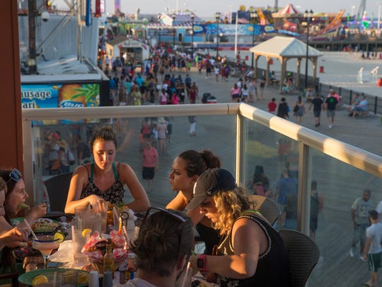 Patrons eat on the balcony of Spicy Cantina with a great view of the boardwalk.