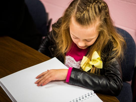 """Calli Larrison, 10, reads """"Charlie and the Chocolate Factory"""" at Ft. Wright Elementary in Covington, Ky. Friday, December 2, 2016. Calli was born with Optic Nerve Hypoplasia, which limits her vision. She has won regional Braille Challenges and has competed in the National Braille competition. Teacher Terri Schemmel says CalliÕs Wish List item Ð a refreshable Braille note taker."""