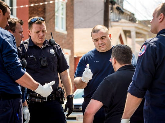 Tyler Neff (center), of the Covington Fire Department, shows the man who overdosed the Narcan the paramedics administered to revive him Thursday, April 13, 2017 in Covington, Kentucky.