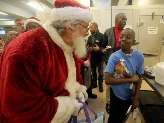 Jameel Richardson, 13, a volunteer server at the annual Eileen Hickey Holiday Dinner at the Lunchbox at the Family Partnership Center in Poughkeepsie, chats with Santa, a.k.a. Ralph Packard of Wappingers Falls after receiving a Christmas present Dec. 25, 2017.