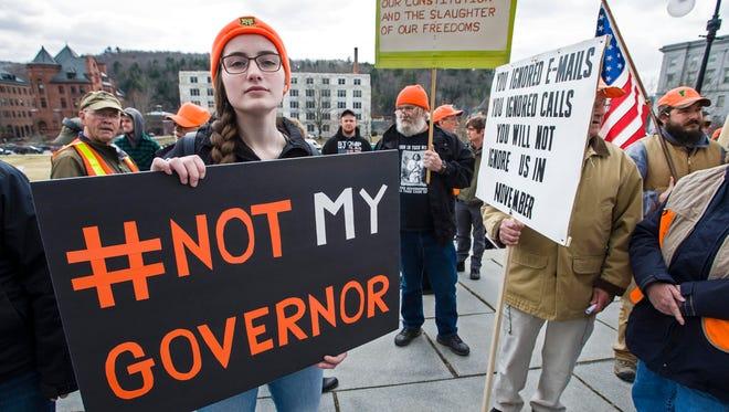 Demonstrators wait for Gov. Phil Scott to sign three gun reform bills on the steps of the Statehouse in Montpelier on Wednesday , April 11, 2018.