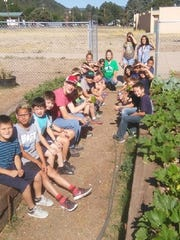 The young gardeners of the Sierra Blanca Boys and Girls Club show off their plants.