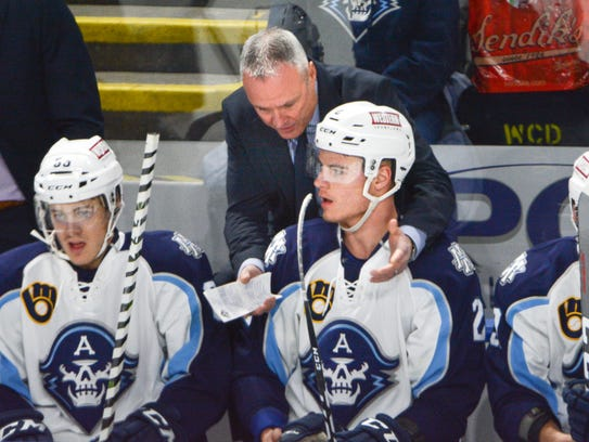 Milwaukee Admirals coach Dean Evason talks with rookie Tyler Moy during a break in the action in a recent game.