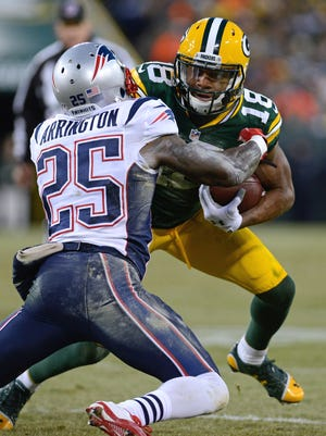 Randall Cobb (18) fights to push past Patriots cornerback Kyle Arrington in the second quarter Sunday atat Lambeau Field.