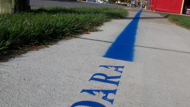 A blue line on downtown Adrian city sidewalks marks the boundary of the Downtown Adrian Refreshment Area. Within these boundaries, alcoholic drinks can be purchased from restaurants and bars and consumed outside. Pictured is the southern end of the DARA along Church Street, heading west past Nova's.
