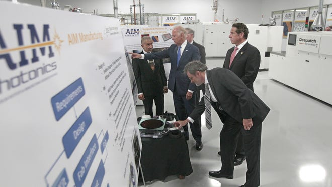 Vice President Joe Biden asks questions as he is briefed by Dr. Alain Kaloyeros, founding President and CEO of SUNY Polytechnic Institute, left, as he visits SUNY Poly Canal Ponds during the official announcement of the Department of Defense awarding a $110 million to help create the new American Institute for Manufacturing Integrated Photonics Monday, July 27, in Rochester, NY.  Also attending the briefing are Michael Liehr, Executive Vice President of Innovation and Technology, Colleges of Nanoscale Science and Engineering, SUNY Polytechnic Institute, right, New York Governor Andrew Cuomo, top right, and Under secretary Frank Kendall.