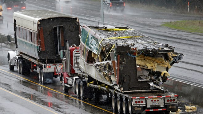Two damaged train cars sit on flatbed trailers after being taken from the scene of an Amtrak train crash onto Interstate 5 a day earlier Tuesday, Dec. 19, 2017, in DuPont, Wash.
