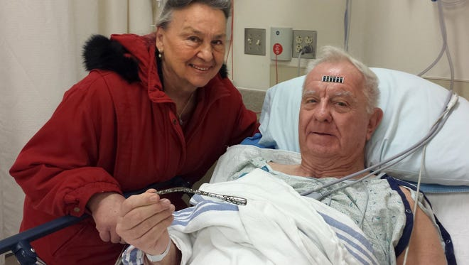 Arthur Lampitt and his wife Betty of Granite City, Mo., show off the 1963 Thunderbird turn signal that was embedded in his arm for 51 years, after having surgery to remove it on Wednesday, Dec. 31, 2014. The 7-inch turn signal was embedded in his arm during a traffic accident that broke Lampitt's hip, drawing attention away from the arm, which healed. (AP Photo/St. Louis Post-Dispatch, Jesse Bogan)  EDWARDSVILLE INTELLIGENCER OUT; THE ALTON TELEGRAPH OUT
