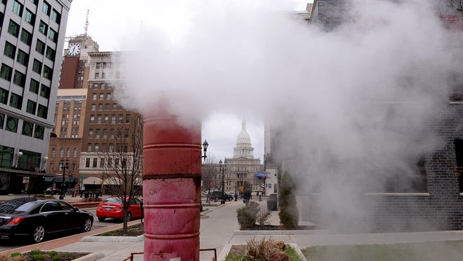 Steam pours from a steam stack on Michigan Avenue between Grand Street and Washington Square in Lansing on Friday, April 10, 2015. BWL will be replacing the steam pipe that leaking, a pipeline that serves all of it's downtown steam customers.