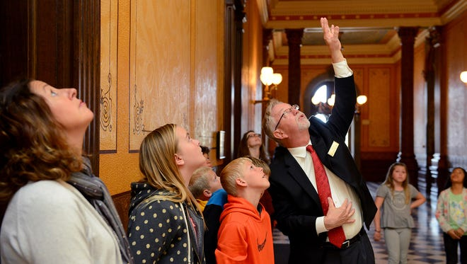 Chris Benson, a longtime Capitol tour guide points out items of interest painted on the ceiling in a hallway on the first floor of the Capitol on Thursday.
