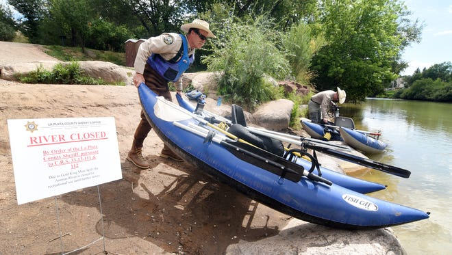 Colorado Parks and Wildlife district wildlife manager Drayton Harrison, front, and area wildlife manager Matt Thorpe prepare to float down the Animas River from the 32nd Street put-in on the north side of town to DoubleTree on the south side on Thursday August 13, 2015, in Durango, Colo. Thorpe said they were looking for dead fish, animals and insects and planned to send anything they found to a lab to have it analyzed. (Steve Lewis/The Durango Herald via AP) MANDATORY CREDIT