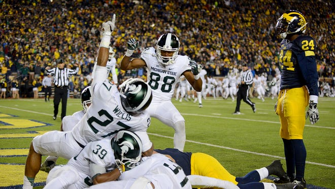 Spartans Khari Willis (27) and Monty Madaris (88) celebrate in the endzone after time expired to beat the Wolverines 27-23 on Oct. 17, 2015, at Michigan Stadium in Ann Arbor.