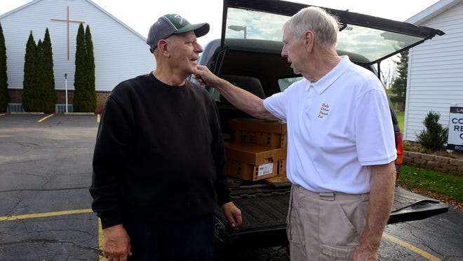 Tom Cullimore, right, talks with Bob Leiby, a volunteer with the Clinton County Food Bank in Bath Nov. 5. Cullimore runs an initiative called HOPE - Help Other People Eat - and picks up food from meat processors and delivers it to food banks. On delivery days, the two meet at a church in Bath and Cullimore gives Leiby his supply for the food bank.