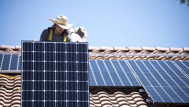James Hewitt moves a solar panel during a rooftop installation in Buckeye in July.