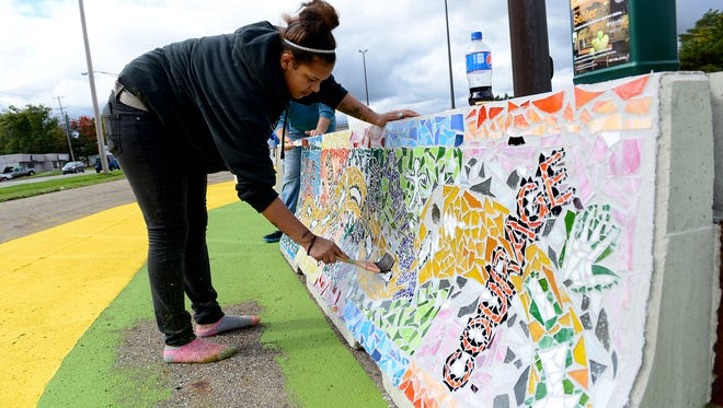 Marissa Nelson-Russell applies sealant to one of the mosaics on Oct. 9 as part of the Project RestART, a partnership between Peckham and the MSU Residential College in the Arts and Humanities and College of Engineering. Project RestART began with ideas back in 2012 and morphed into artistic mosaics on concrete barricades now placed on the Racer Trust site on Saginaw.