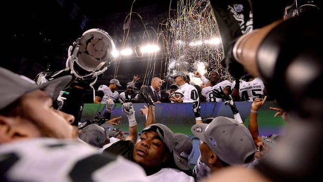 Tight end Josiah Price celebrates in the foreground as Big Ten Commissioner Jim Delaney hands coach Mark Dantonio the Big Ten Championship trophy December, 5, 2015, in Indianapolis after MSU's 16-13 win over Iowa in the Big Ten Championship football game.