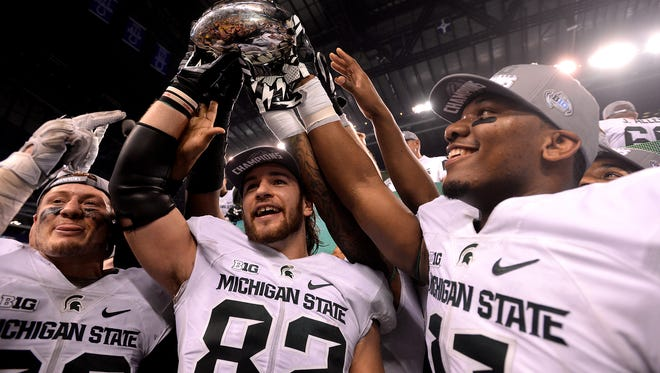 Tight ends Josiah Price (82) and Jamal Lyles (11) hold the Big Ten Championship trophy December, 5, 2015, in Indianapolis after MSU's 16-13 win over Iowa in the Big Ten Championship football game.