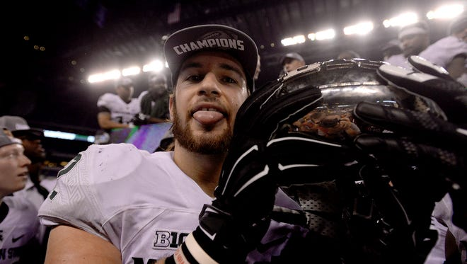 Tight end Josiah Price poses with the Big Ten Conference Championship trophy Saturday in Indianapolis after MSU's 16-13 win over Iowa in the Big Ten Championship football game. MSU's is two more wins from a national championship.