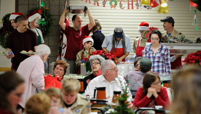 Boy Scouts from Troop 20 in Waite Park serve their annual Christmas Dinner at St. Joseph's Catholic Church in 2014.