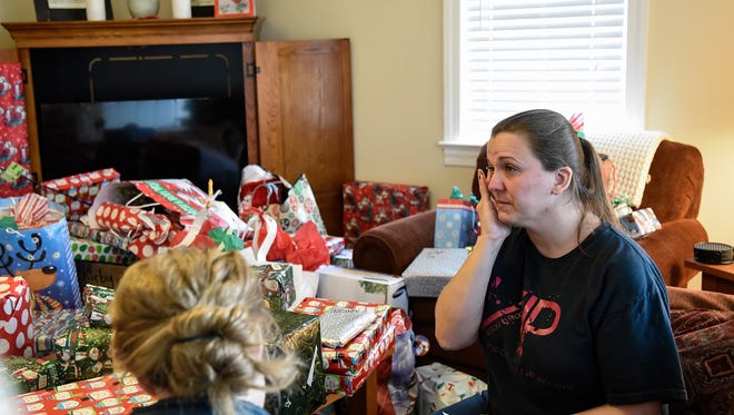 Amy Scarbro tears up after  she and her husband, Chris, and their 5 children aged 6 to 20 received gifts delivered by the Christiana Fire Company and Aetna Hose, Hook & Ladder after the family lost everything in a recent house fire.