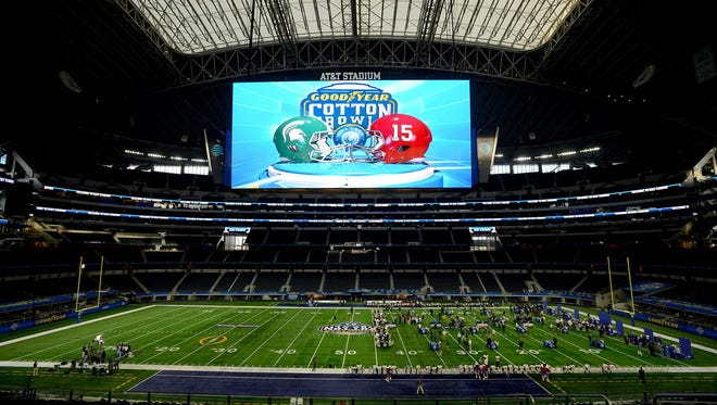 Michigan State players and coaches sit on the field at AT&T Stadium for the Cotton Bowl Media Day on Tuesday, Dec. 29, 2015, at in Arlington, Texas.
