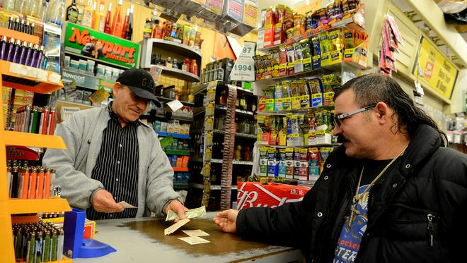 """Thomas Kara hands Sergio Leyva his Powerball tickets on  Friday, Jan. 8 at Sunset Food Mart on Kalamazoo Street in Lansing. The jackpot is at $800 million and Leyva said, with a laugh, that with his winnings he'd buy """"a lot of something."""""""