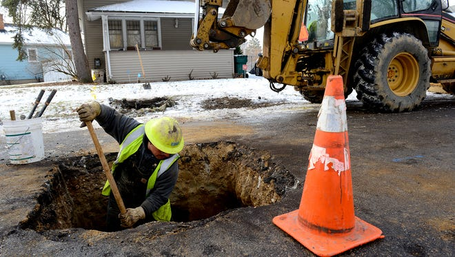 Richard Garza, a BWL mechanic, moves dirt around the water main after replacing the lead water pipe with a new copper one  Friday, Jan. 22, 2016 at a home on Greencroft in Lansing. Since 2004 the BWL has been replacing lead lines with copper ones and has less than 500 lead lines that it plans to replace by 2017.