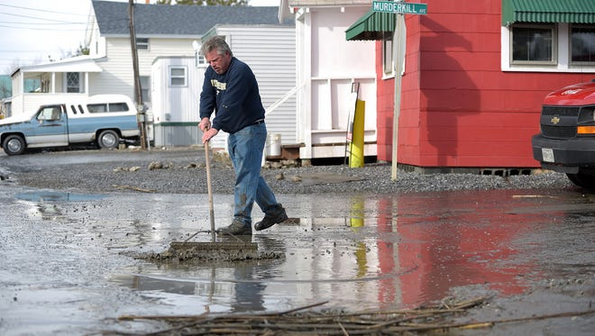 Luke Fistere, owner of the Bayview Inn Tavern in North Bowers, cleans up mud and sludge from outside the tavern on Monday.