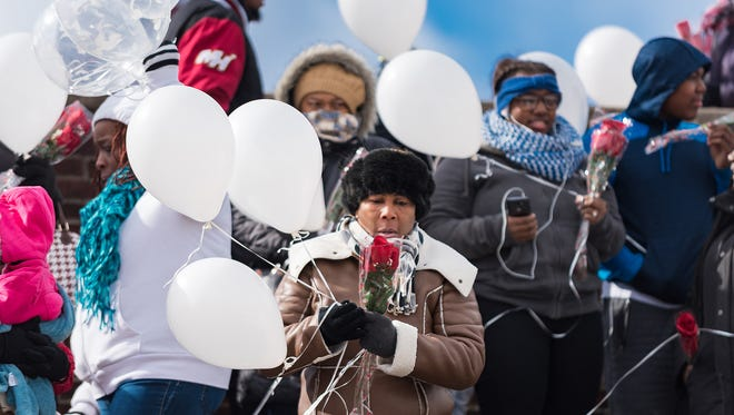 Patricia Brown of Wilmington holds balloons before giving a group prayer. Survivors of gun violence in Wilmington release balloons in memory of loved ones lost in a ceremony at P.S. Dupont Middle School's football field on Saturday afternoon.