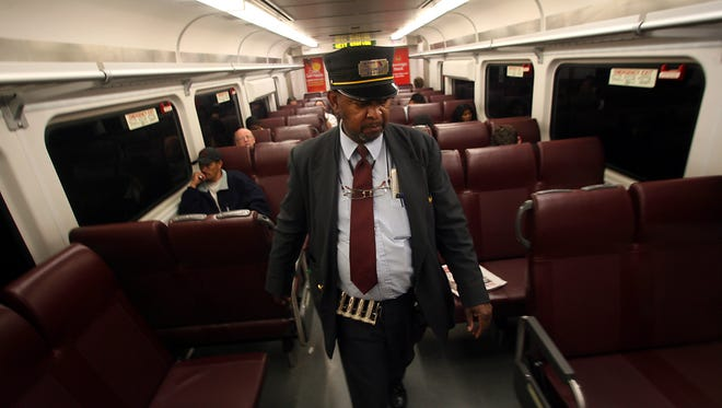 Assistant Conductor Harold Howard walks to the back of a NJ Transit  train car to open the doors at a stop.